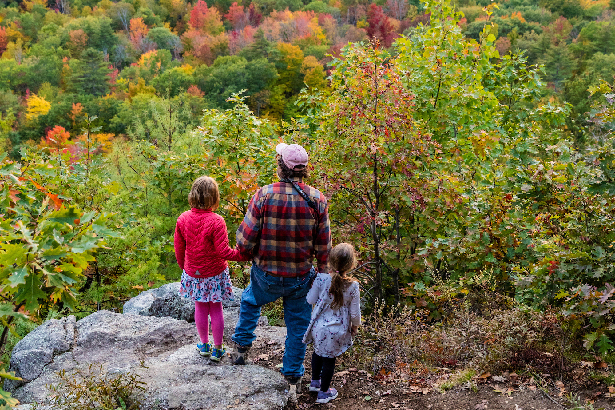 A man and his two granddaughters check out the view from Pismire Bluff in the Raymond Community Forest in Raymond, Maine.